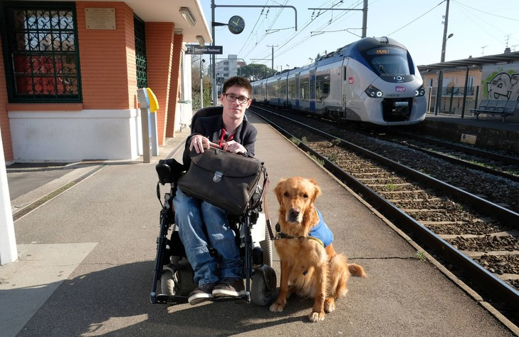 Kevin Fermine pose avec son chien Djembe, sur le quai de la gare de Toulouse-Saint-Agne, le 16 mars 2017. / Eric Cabanis/AFP